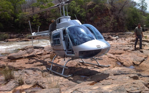 Image of a survey helicopter landing next to a fast flowing river in Africa