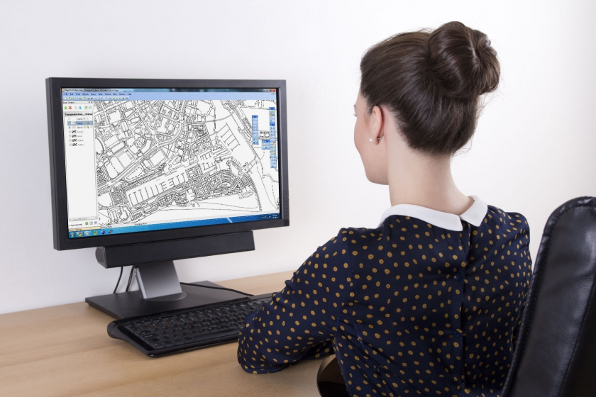 Female looking at PC screen of digital mapping data streamed by WFS feeds