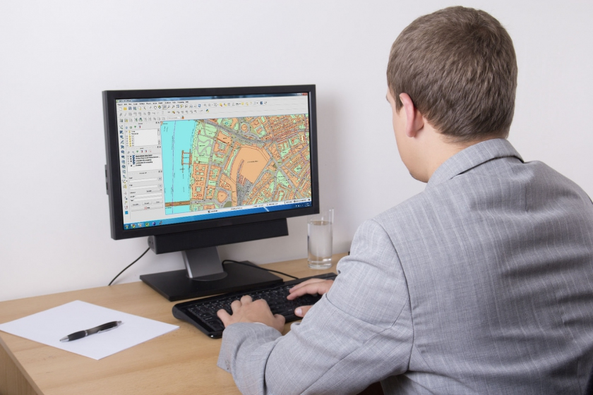 Man looking at PC screen of digital mapping data streamed by WMS feeds