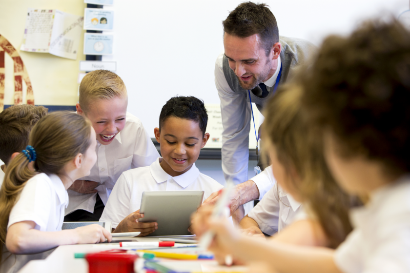 picture of teacher looking at an ipad with school children